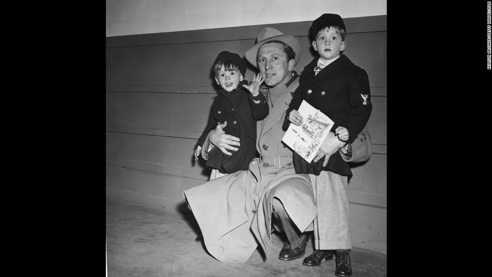 Douglas kneels beside his sons, Joel, left, and Michael, circa 1955. Joel and Michael followed their father's career path and became actors.
