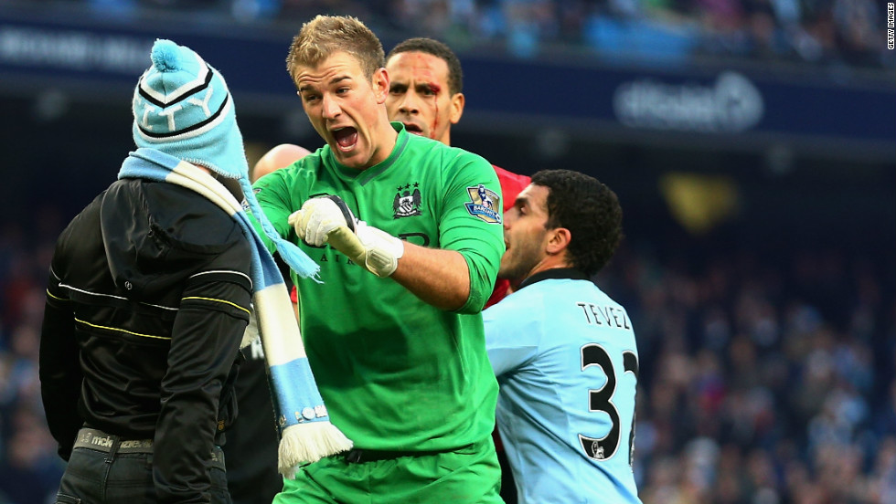 Manchester City goalkeeper Joe Hart of  confronts a pitch invader at the end of his side's 3-2 derby defeat by Manchester United, whose defender Rio Ferdinand (at back) was left with a bloody face after being hit by a coin thrown from the crowd.
