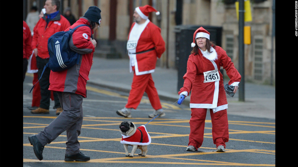 A woman and her dog in Santa suits prepare for the annual Glasgow Santa Dash on December 9 in Glasgow, Scotland.