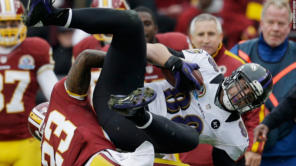 Ravens tight end Dennis Pitta is tackled by Redskins cornerback DeAngelo Hall after catching a first-half pass on Sunday.