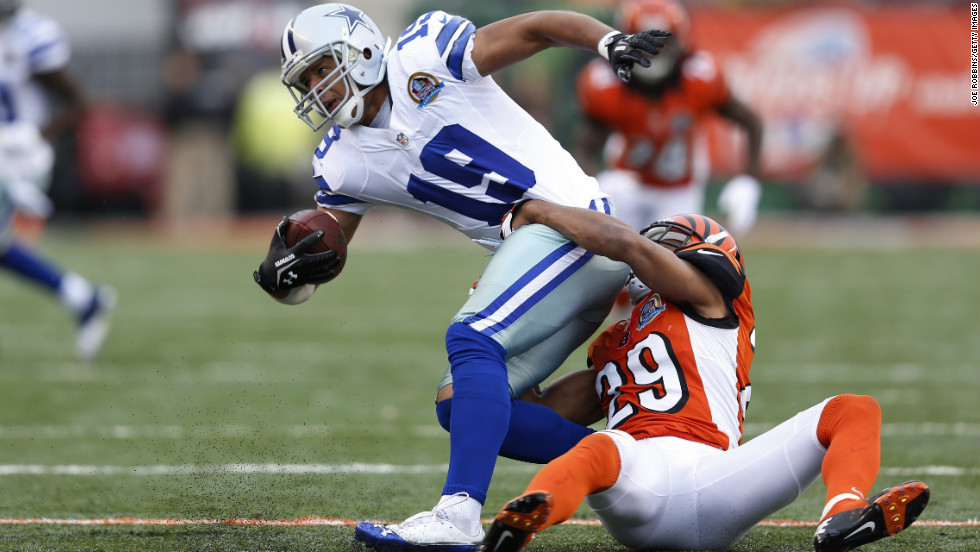 Miles Austin of the Cowboys gets tackled by Leon Hall of the Bengals on Sunday.