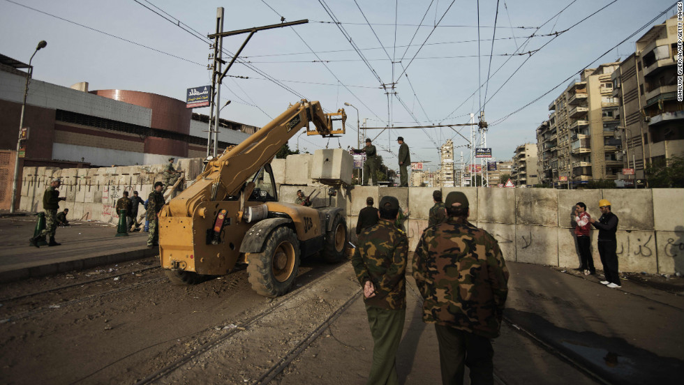 Egyptian army engineers and soldiers build a third line of concrete blocks outside of the Egyptian presidential palace in Cairo in preparation for more protests on December 9.