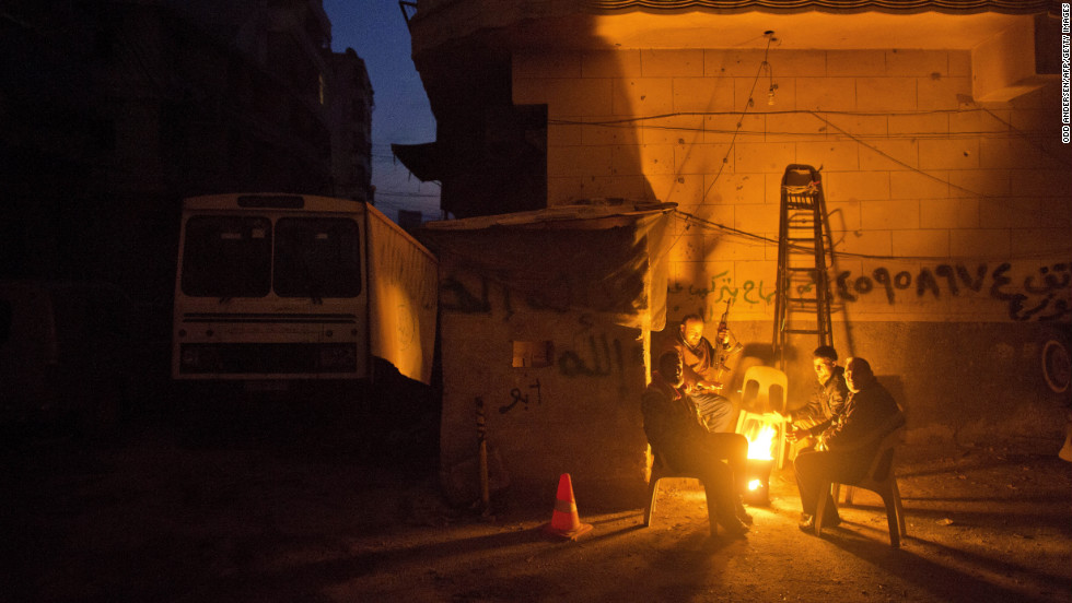 Men warm themselves by a fire on a street corner in Aleppo, Syria, on Sunday, December 9.