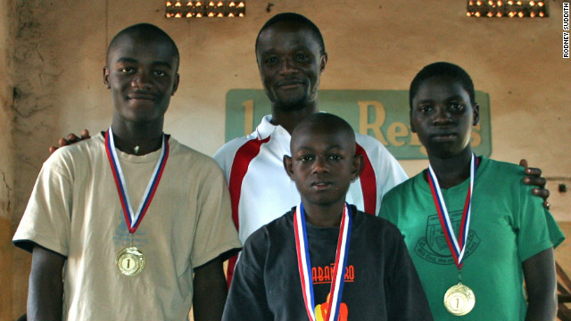 Robert Katende (center, rear) and Phiona Mutesi (right) after the 2009 International Children's Chess Tournament in Sudan.