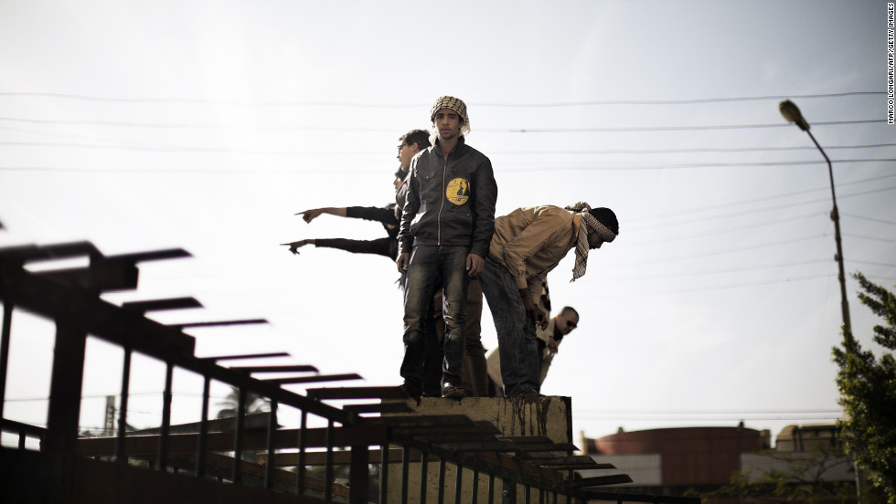 Protesters opposed to Egypt's president demonstrate on top of a barricade erected by the Egyptian army to protect the presidential palace in Cairo on December 11.