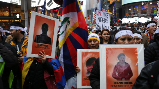 Protesters carrying posters of Tibetans who have self-immolated walk to the United Nations in New York on December 10, 2012.