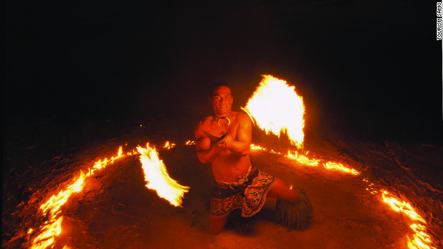 A fire dancer performs on a beach in Samoa.