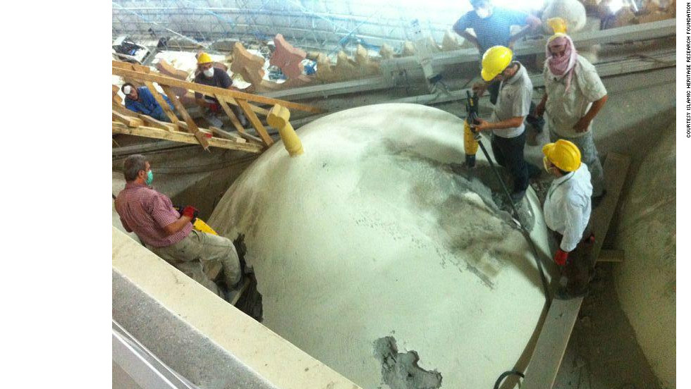 Workers drill into one of the portico's domes from above as part of the demolition process.