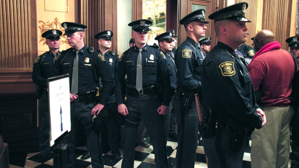 Michigan State Police guard the entrance to the House chamber as protestors fill the building.