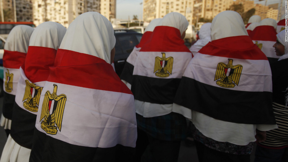 Girls walk with Egypt's national flag draped over their backs to a rally for supporters of President Mohamed Morsy in Cairo on Tuesday, December 11.