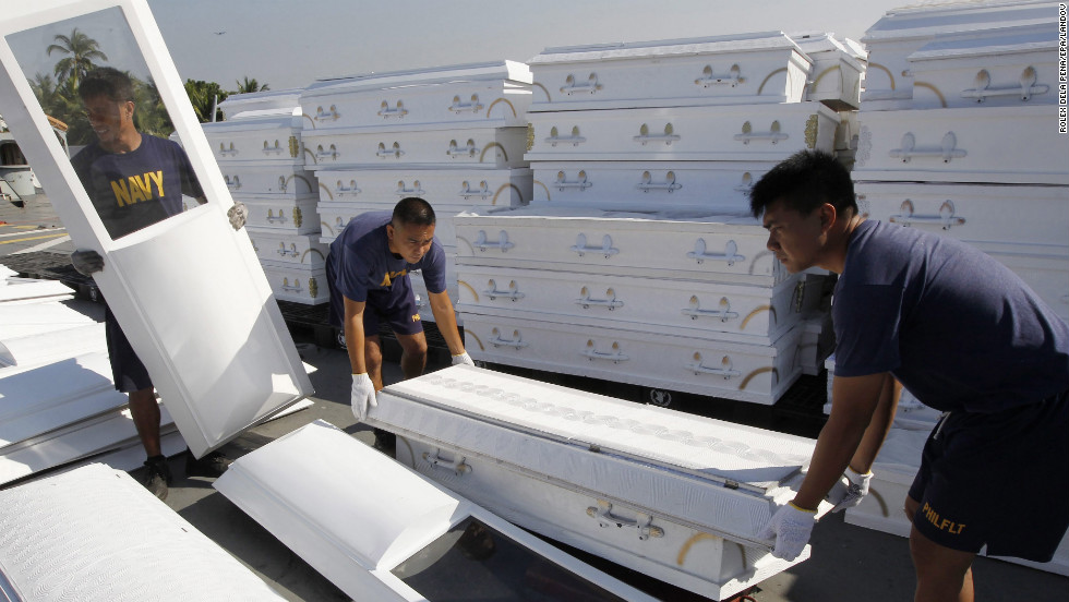 Philippine navy personnel arrange donated coffins aboard the BRP Laguna, which is set to transport relief supplies from a base in Cavite City, on Tuesday, December 11, in the aftermath of Typhoon Bopha.