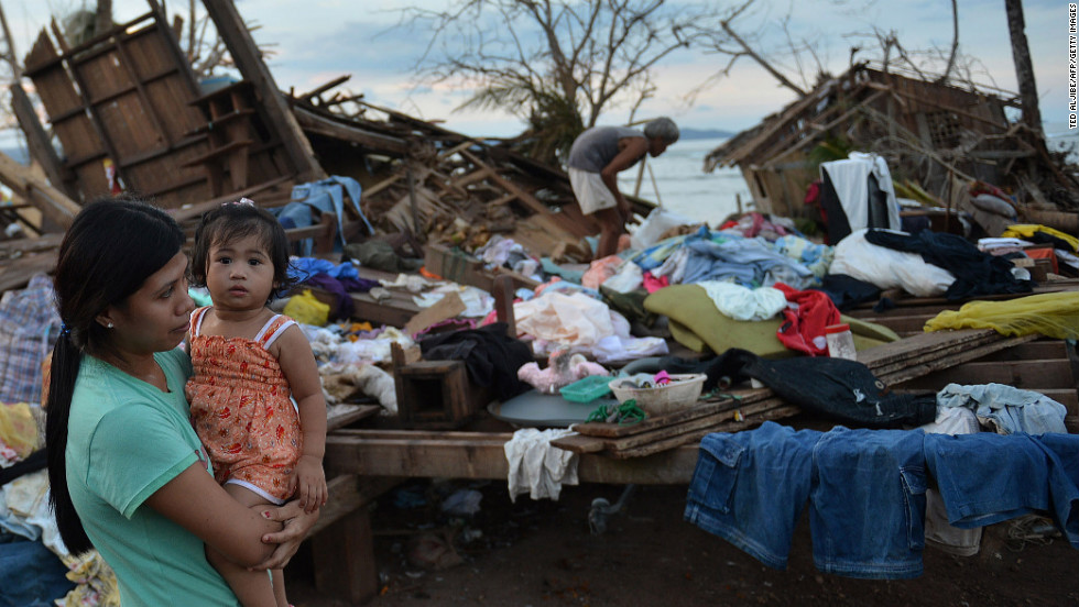 A woman stands next to her destroyed house in Boston, Davao Oriental province, on December 11.