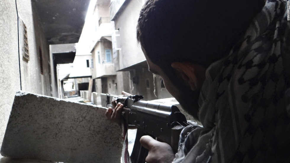 A Free Syrian Army fighter takes position as he aims his weapon in Aleppo's al-Amereya district on Tuesday, December 11.