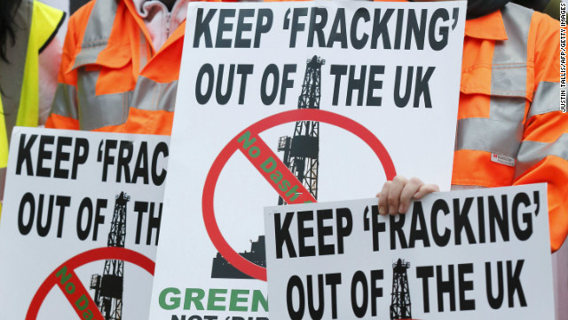 Demonstrators hold placards in protest against fracking outside Parliament in London on December 1, 2012.