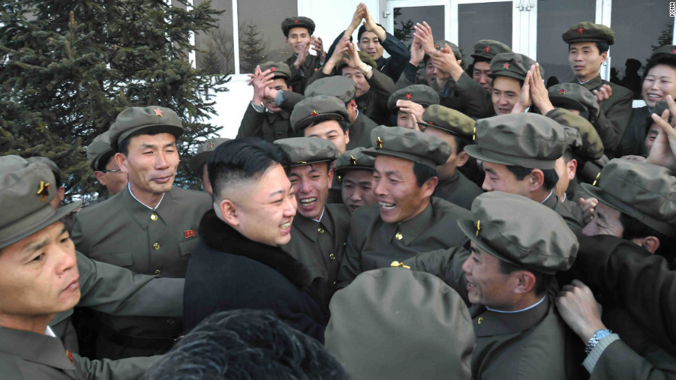 Well-wishers mob a smiling North Korean leader Kim Jong Un (without hat) on Wednesday after the successful launch of the country's first satellite.