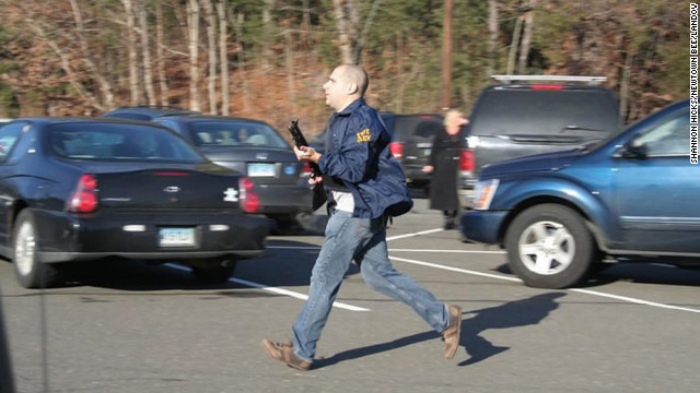 A Connecticut State Police officer runs with a shotgun at the Sandy Hook Elementary School in Newtown on Friday, December 14.