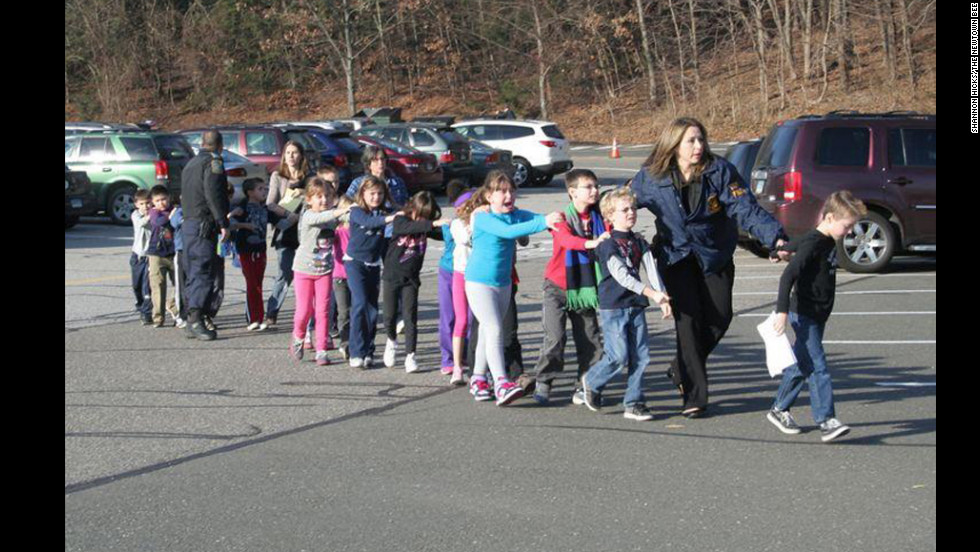 State police personnel lead children from the school.