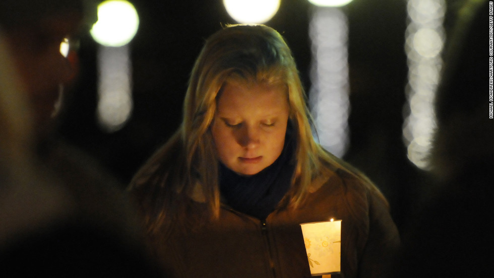Corinne McLaughlin, a student at the University of Hartford, bows her head during a candlelight vigil at Hartford, Connecticut's Bushnell Park on Friday, December 14, honoring the students and teachers who died at Sandy Hook Elementary School in nearby Newtown earlier in the day.