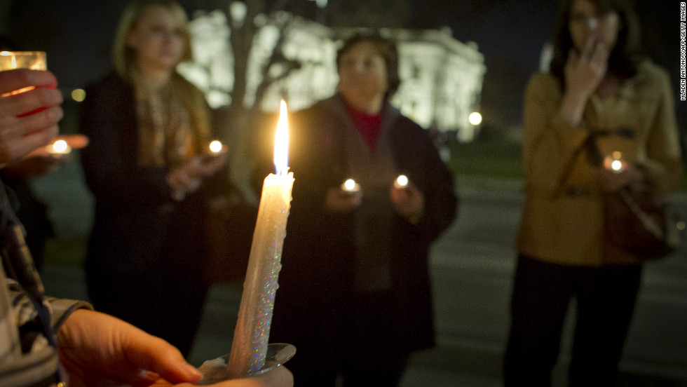 Candles burn as people gather for a vigil outside the White House.