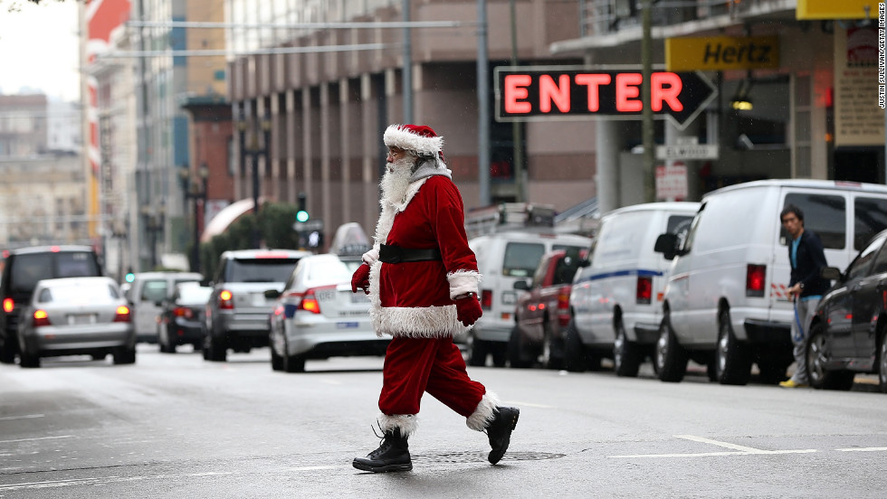 A man decked out as Santa walks down Geary Street on December 14 in San Francisco.