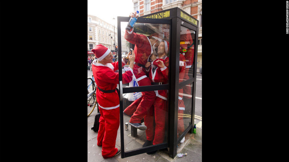 Costumed Santas crowd into a telephone booth during the Santacon pub crawl near London's Trafalgar Square on December 15.