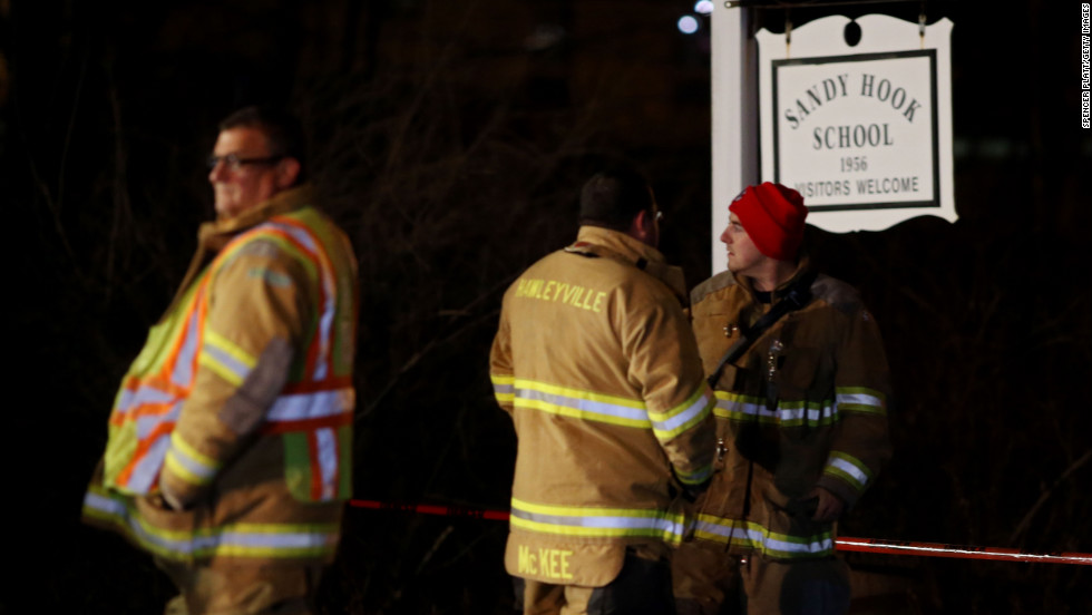 Emergency workers stand in front of the Sandy Hook Elementary School in Newtown.