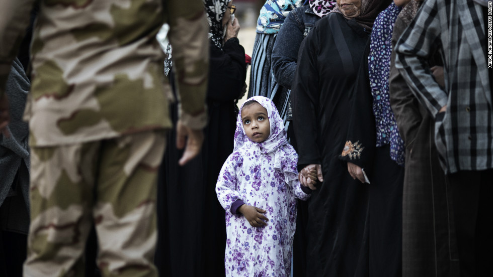 An Egyptian girl waits with relatives queuing to vote at a polling station in central Cairo n December 15, 2012.