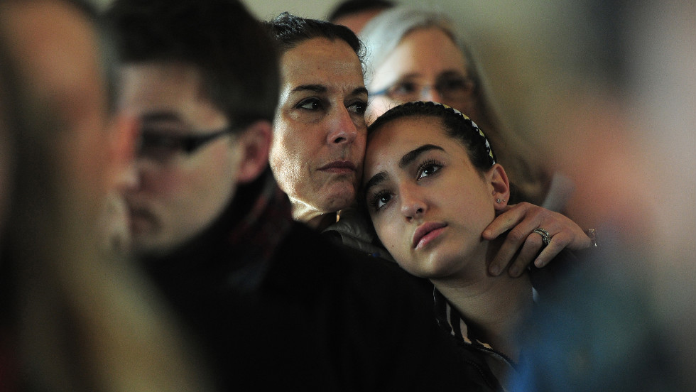 A mother and daughter attend a prayer service at St. John's Episcopal Church in Newtown on Saturday.