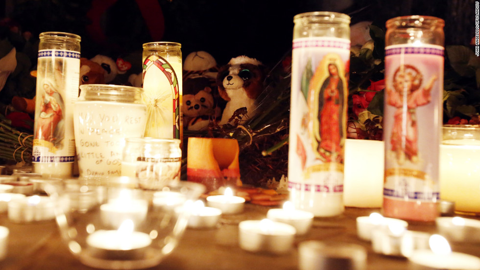 Candles light up a memorial outside of Saint Rose of Lima Church in Newtown.