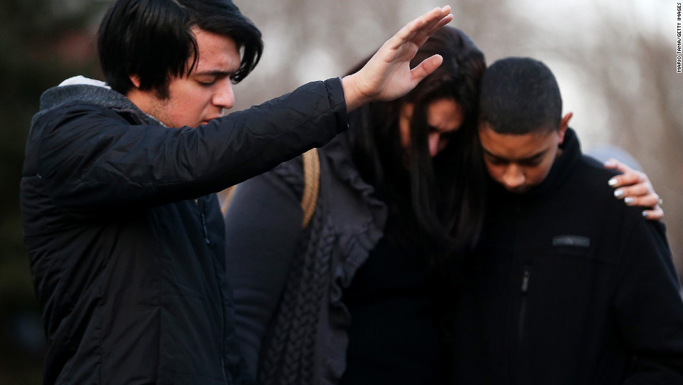 Lucas, Kelly and Michael DaSilva pray and embrace at a makeshift memorial near the school in Newtown.