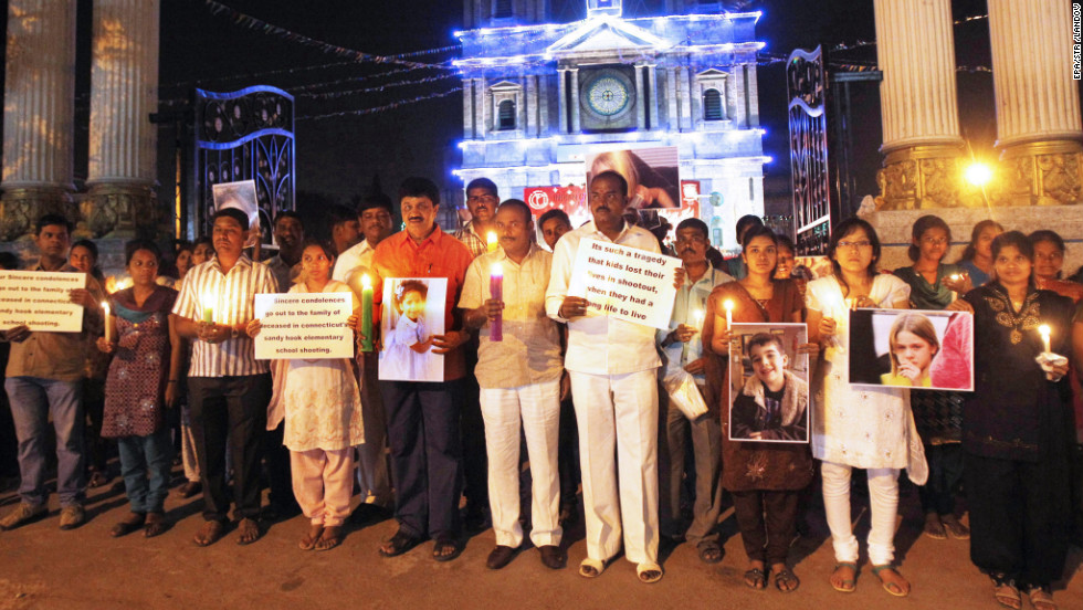 People in Bangalore, India, hold cards and photographs of the slain at a candlelight vigil outside a Catholic church on December 16.