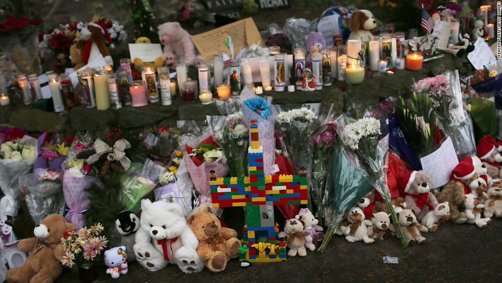 Teddy bears, flowers and candles in memory of those killed are left at a memorial down the street from the school on December 16.