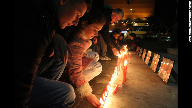 Albanian children light candles as pay their respects to the victims of a elementary school shooting in Newtown, Connecticut.