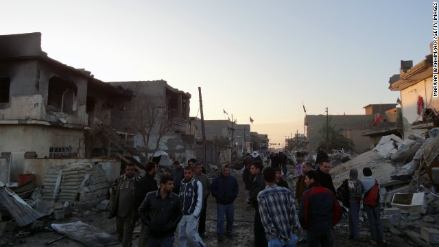 Iraqis inspect damage after two bomb blasts in the town of Tuz Khurmato in Kirkuk province Monday.