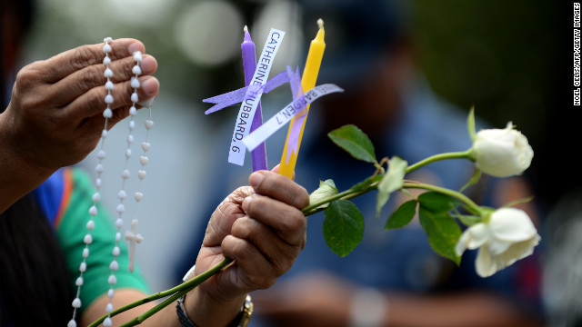 Members of human rights group, Volunteers Against Crime and Corruption (VACC), light candles with names of those killed during the shooting at Sandy Hook Elementary School in Newtown, Connecticut in the US, during a prayer vigil in front of the US Embassy in Manila on December 18, 2012.