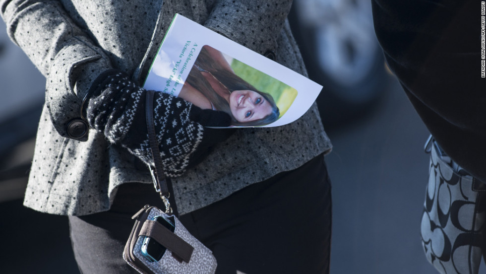 A woman carries a program with Soto's photo after attending a funeral for the slain teacher in Stratford on December 19.