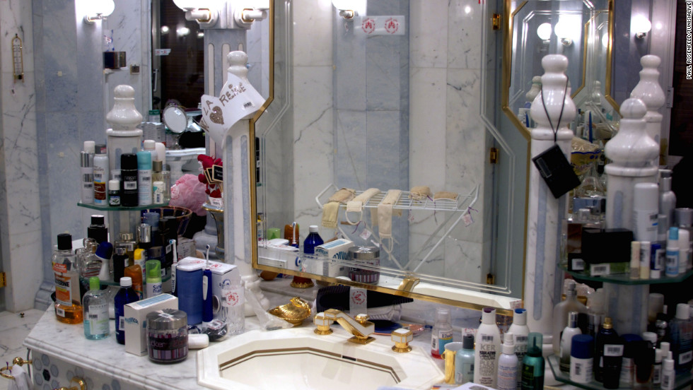 "The palace's main bathroom, which remains as it was when the Ben Ali family abandoned it. The item hanging from the post to the left of the mirror reads: ""La reine"" (the queen)."