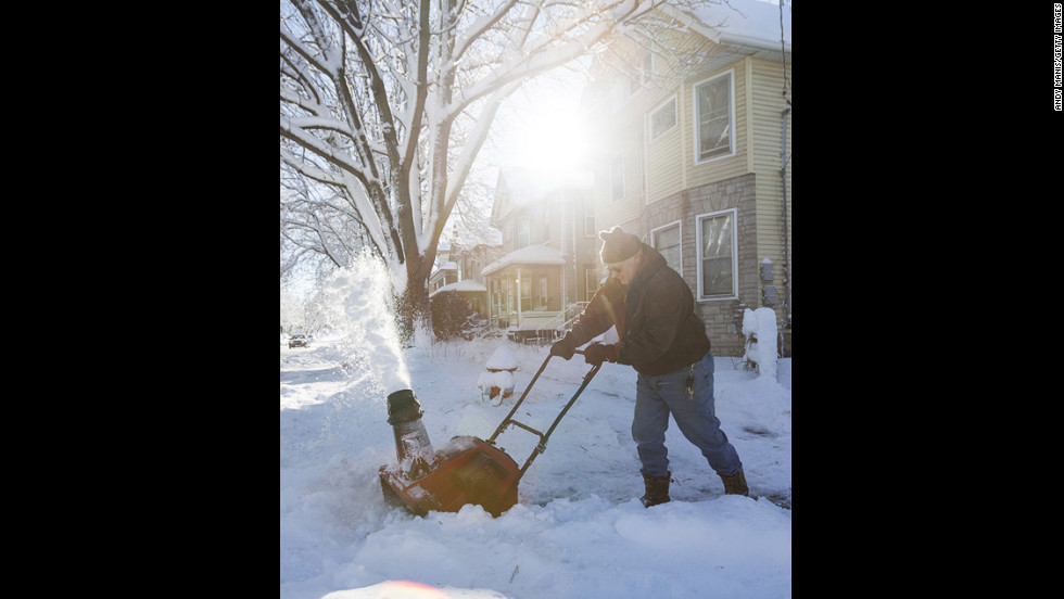 Dave Anderson uses a snow blower to clean the sidewalk in Madison, Wisconsin, on Friday.