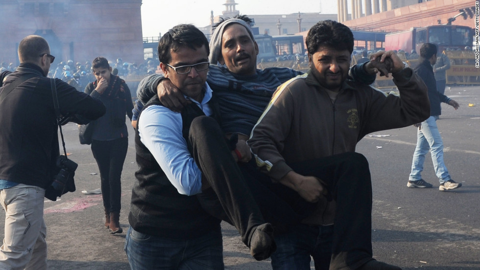 Indian demonstrators carry an injured man from the scene on December 22.