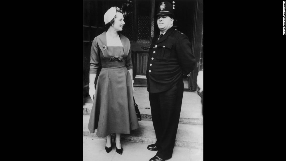 Thatcher chats with a police officer outside the House of Commons, where she took a seat as a member of Parliament for Finchley in October 1959.