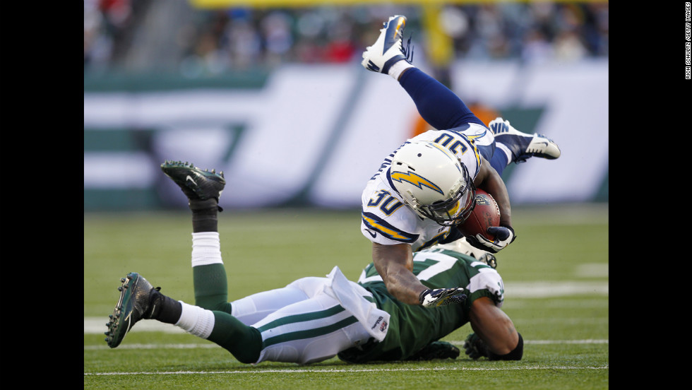 Running back Ronnie Brown of the Chargers is upended by Yeremiah Bell of the Jets during the first half on Sunday.