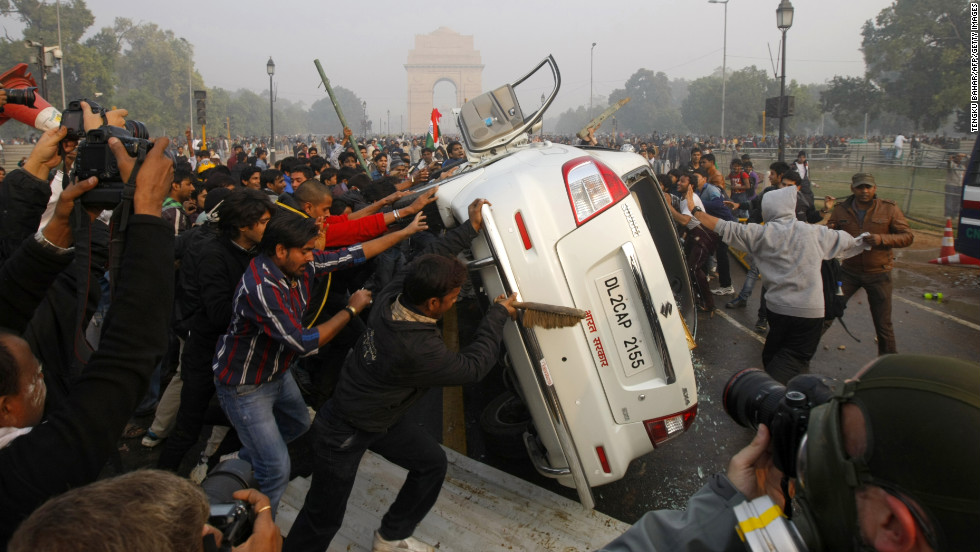 Demonstrators turn a car over on December 23.