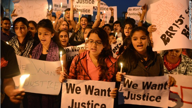 Indian youth hold candles and placards as they take part in a candle light vigil following the gang rape of a student last week in the Indian capital during a rally in Ahmedabad on December 23, 2012.
