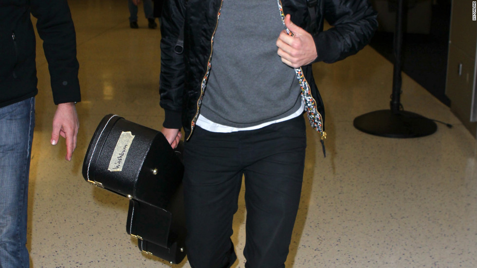 Robert Pattinson wears sunglasses at the airport.