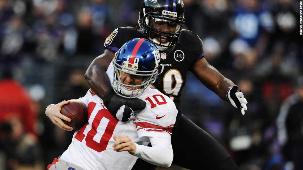 Quarterback Eli Manning of the Giants is pulled down by linebacker Dannell Ellerbe of the Ravens on Sunday.