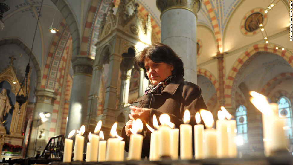 A woman lights candles after a Christmas Mass at Sarajevo's Cathedral of The Heart Of Jesus.
