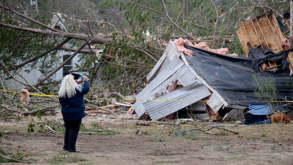 A woman takes a photo of a trailer home destroyed by a tornado near Troy, Alabama, on December 26.