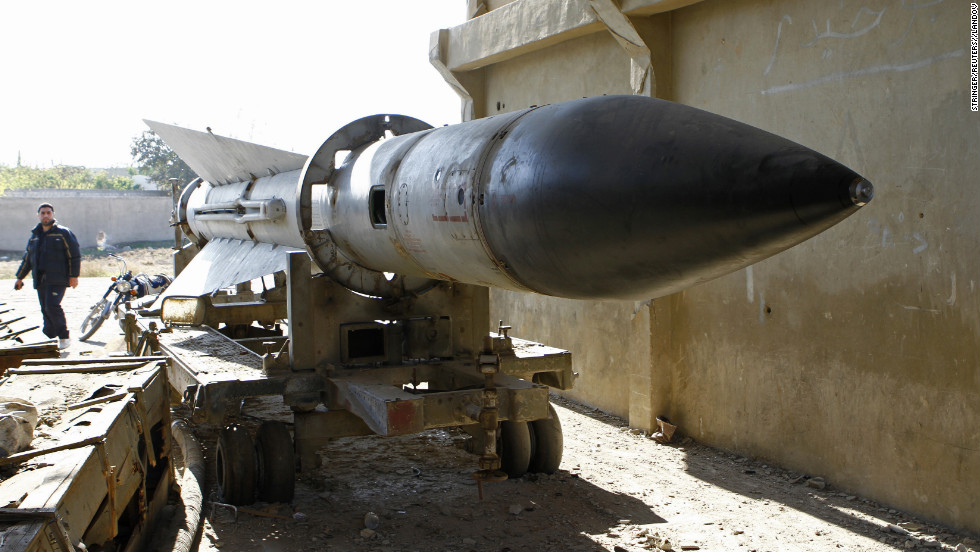 A man walks near a missile on Tuesday, December 25, at an army barracks outside Damascus, Syria, that has been taken over by the Free Syrian Army.