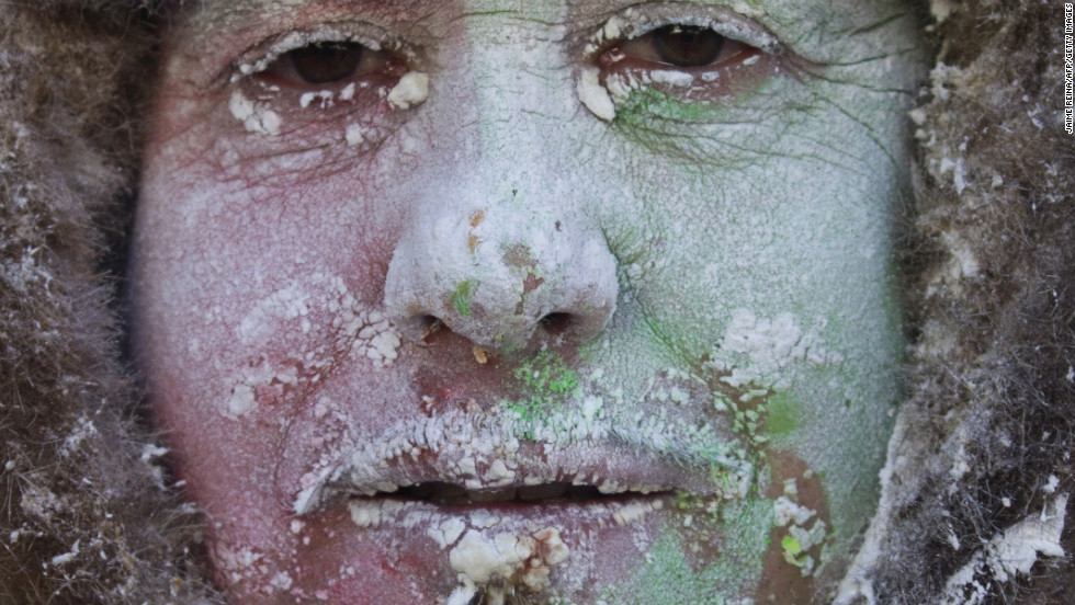 A military-dressed man with flour and eggs on his face poses for a photograph on December 28.