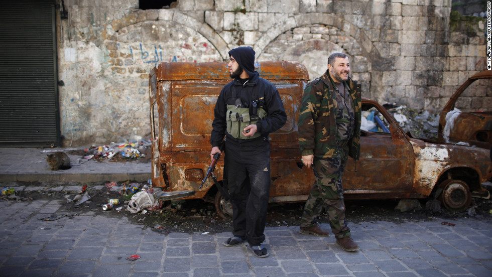 Free Syrian Army fighters stand near damaged cars in Aleppo on Thursday, December 27.
